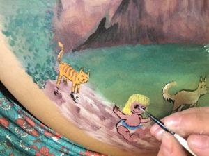mano de la creadora con pincel pintando sobre el vientre de una embaraza la escena de una nina un gato y un perro en un gorc piscina natural